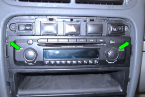 2. Remove 2 screws holding the stereo in the dashboard frame (green arrows)
