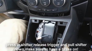 Press in shifter to release trigger and pull shifter down, make sure to have a brake on