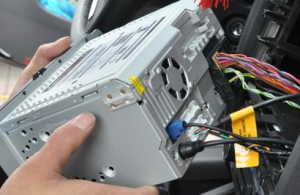 There are connectors and cables at the back of the radio. Remove them