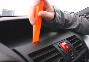 Use a plastic removal tool to pry the trim panel of the original car radio